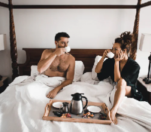 man and lady drinking coffee in bed